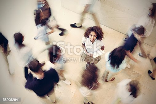istock Nervous student standing still in busy private school hallway 532052841