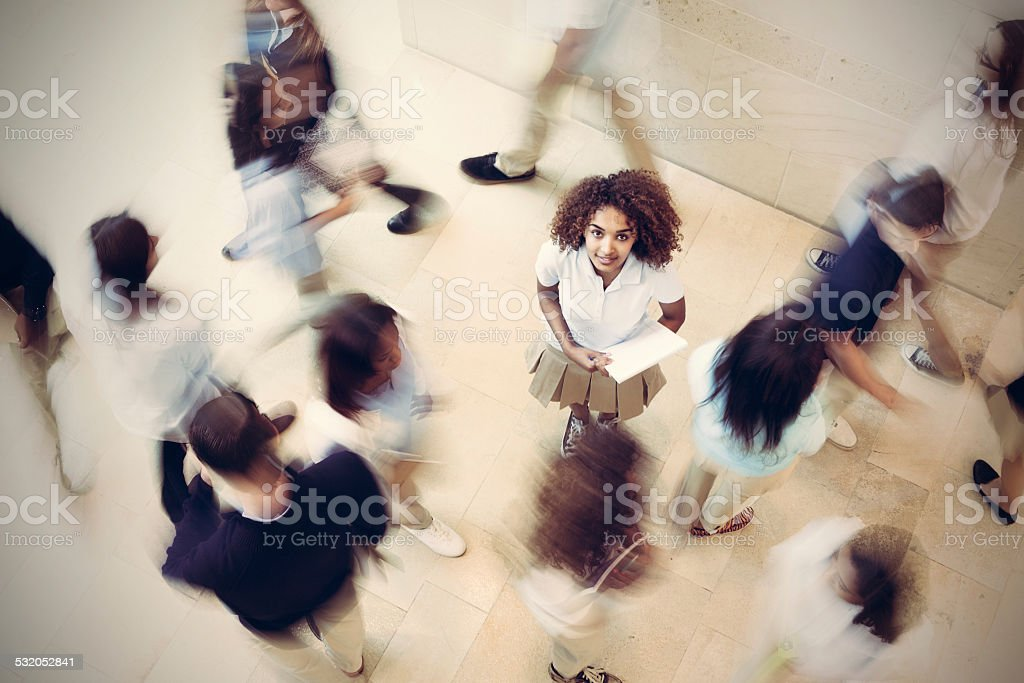 Nervous student standing still in busy private school hallway stock photo
