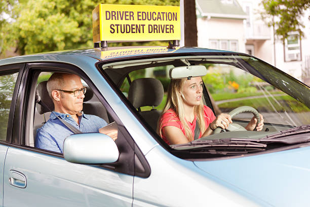 Nervous Teen Driver Taking Driving Examination with Examiner A young teenager girl behind the wheel of a car, learning to drive while a driver's training examiner scores performance in a student driving examination in the Midwest, USA. driving instructor stock pictures, royalty-free photos & images