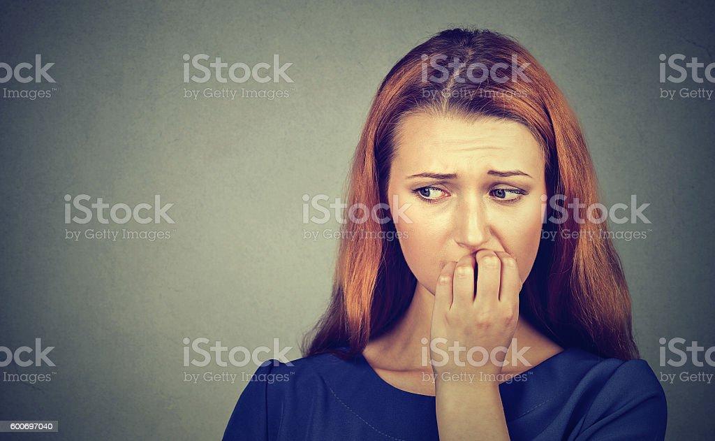 Nervous woman biting fingernails craving or anxious stock photo