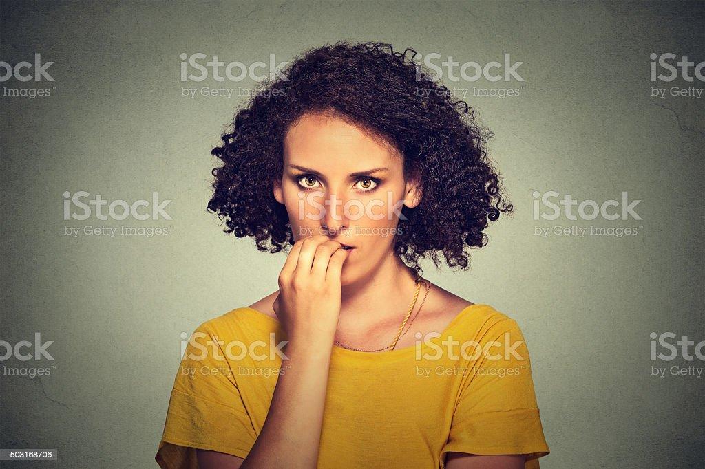 nervous woman biting her fingernails craving something anxious stock photo