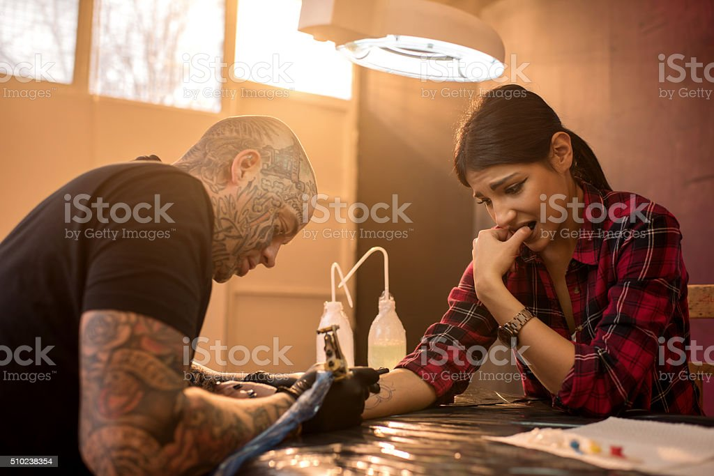Nervous woman getting her arm tattooed in tattoo studio. Afraid woman in tattoo studio getting tattoo on her arm. Adult Stock Photo
