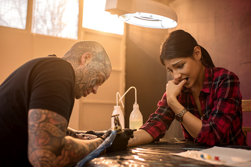 Nervous Woman Getting Her Arm Tattooed In Tattoo Studio Stock Photo - Download Image Now