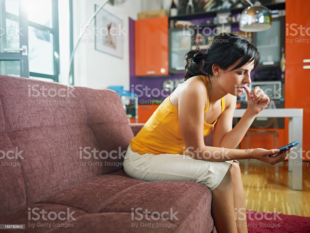 A nervous woman holding her phone waiting for a text message stock photo