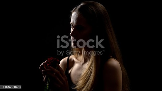 Nervous woman holding red rose from ex-boyfriend, isolated on black background