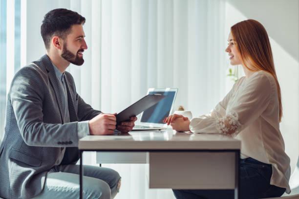 nervös kvinna tittar på chef läsa hennes cv under en anställningsintervju på kontoret - job interview bildbanksfoton och bilder
