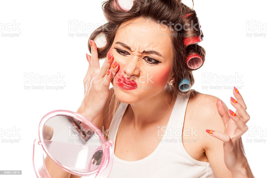 Nervous woman with curlers removing makeup with her hands stock photo