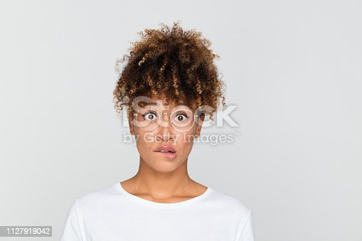 Close up portrait of young afro american woman looking nervous, biting her lips and looking at camera on gray background.