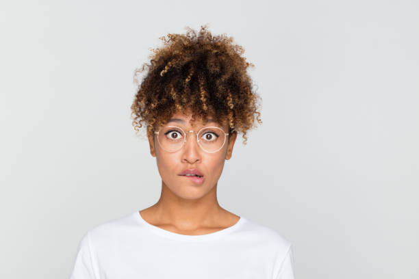 Nervous young african woman Close up portrait of young afro american woman looking nervous, biting her lips and looking at camera on gray background. embarrassment stock pictures, royalty-free photos & images