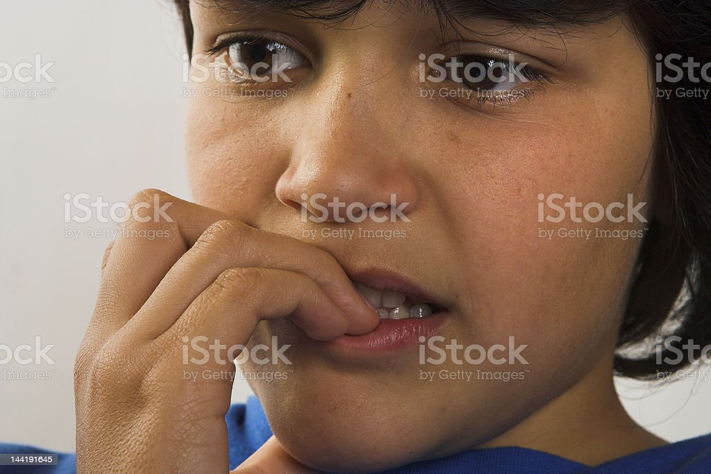 Nervous young kid biting his nails stock photo