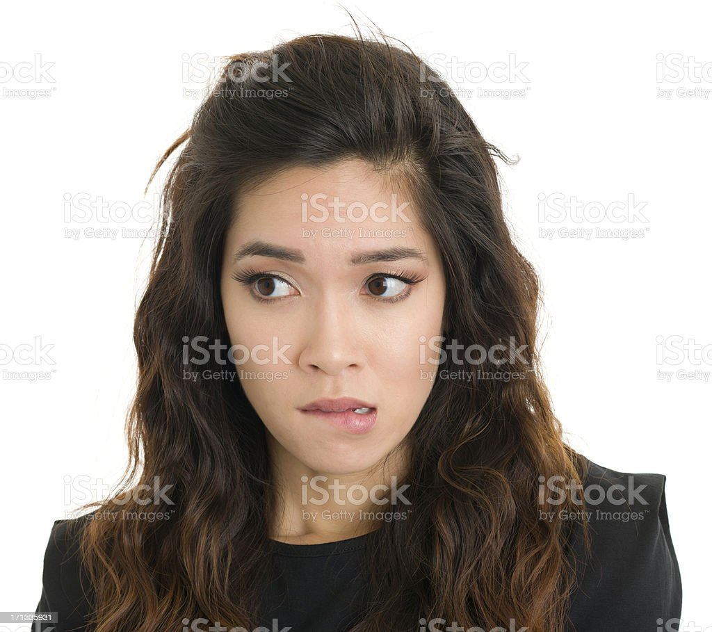 Nervous Young Woman Bites Lip And Looks Sideways stock photo