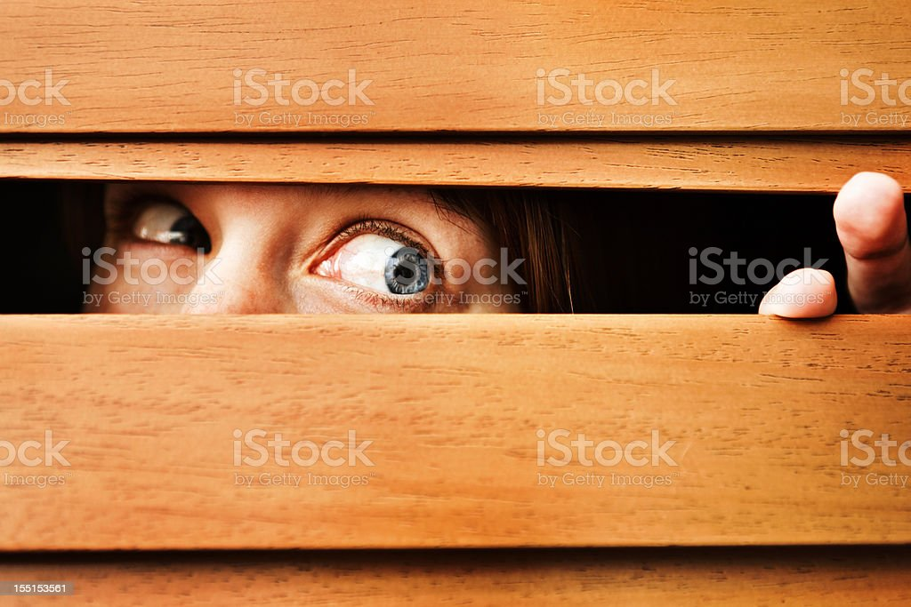 Nervous young woman looking to side through wooden blinds royalty-free stock photo