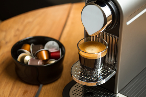 Copenhagen, Denmark - July 8, 2014: Freshly brewed espresso in glass standing on silver Nespresso coffe machine. Blurred background with Nespresso capsules in black bowl.