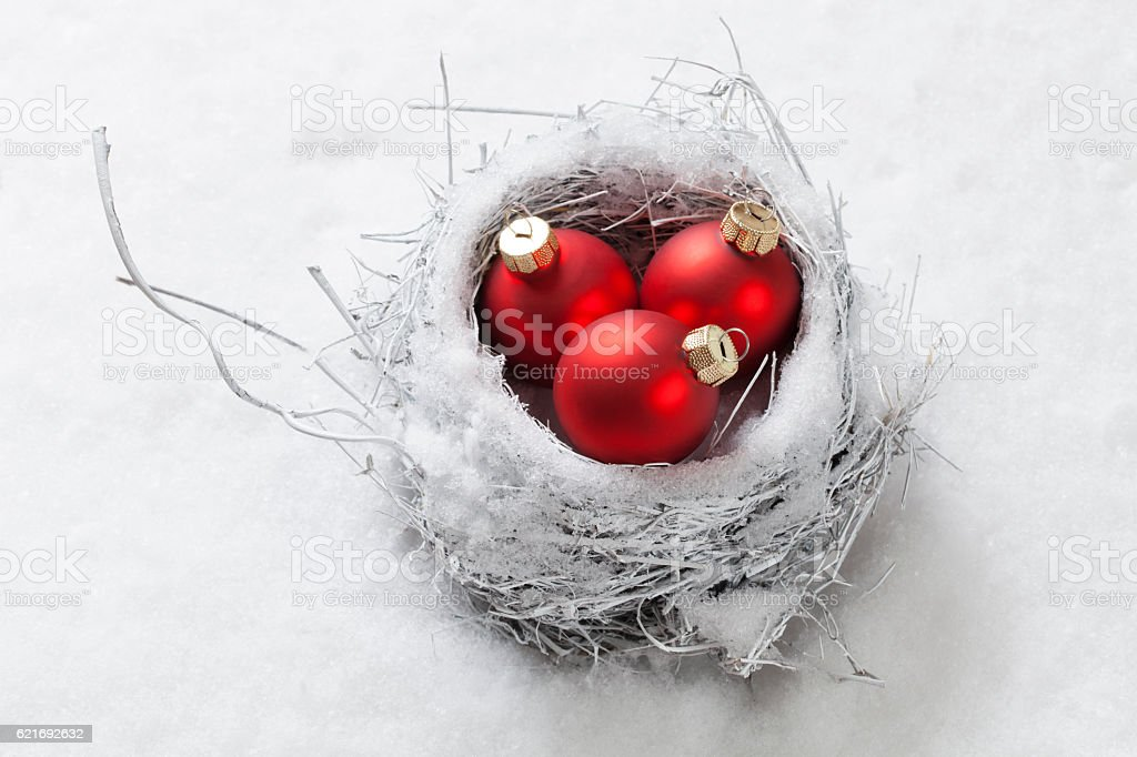 Nest in the snow with Christmas balls stock photo