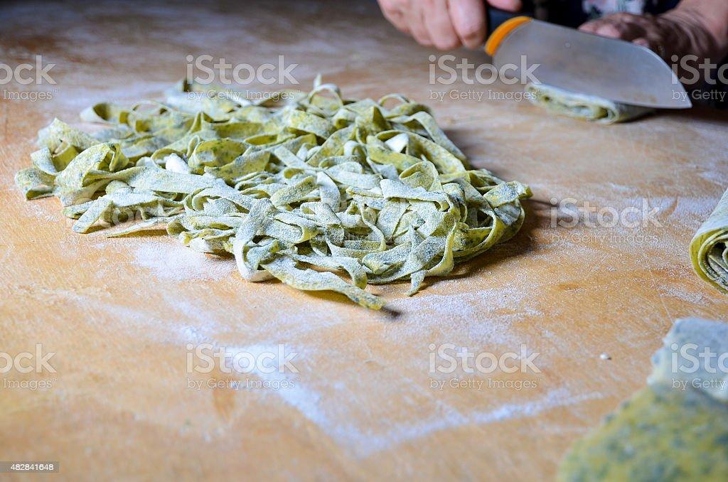 nest of fresh nettle noodles on cutting borad stock photo