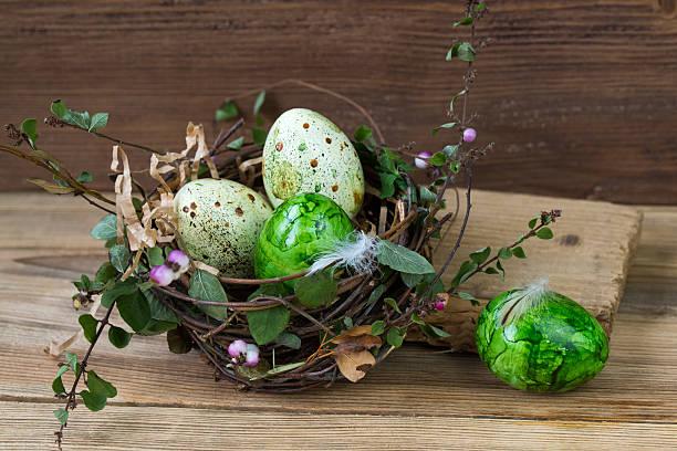 nest with colored easter eggs, wooden background - schöne osterbilder stock-fotos und bilder