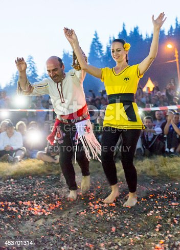 Rijen, Bulgaria - July 18, 2015: A nestinar woman with a child is walking on fire during a nestinarstvo show. The fire ritual involves a barefoot dance on smouldering embers performed by nestinari.