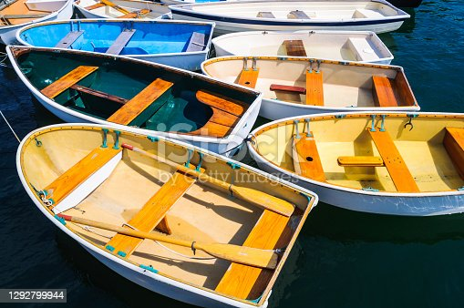 A group of small row boats are nestled closely together at a pier in Quissett Harbor in Falmouth, Massachusetts