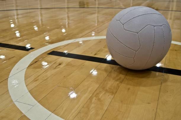 een netball bal geplaatst in het midden cirkel van een indoor netball hof - netball stockfoto's en -beelden