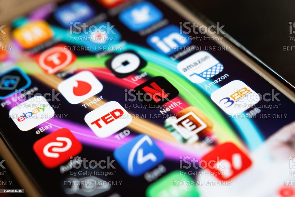 Netflix application showing on screen smart phone on desk at home. Netflix being popular internationally. stock photo