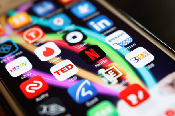 Netflix application showing on screen smart phone on desk at home. Netflix being popular internationally. Chiang Rai: Netflix application showing on screen smart phone on desk at home. Netflix being popular internationally. netflix stock pictures, royalty-free photos & images