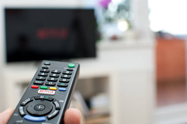 Netflix button on a TV remote with television. Zagreb, Croatia - March 5, 2016: Photo of a Netflix button on a TV remote with television in the background. netflix stock pictures, royalty-free photos & images