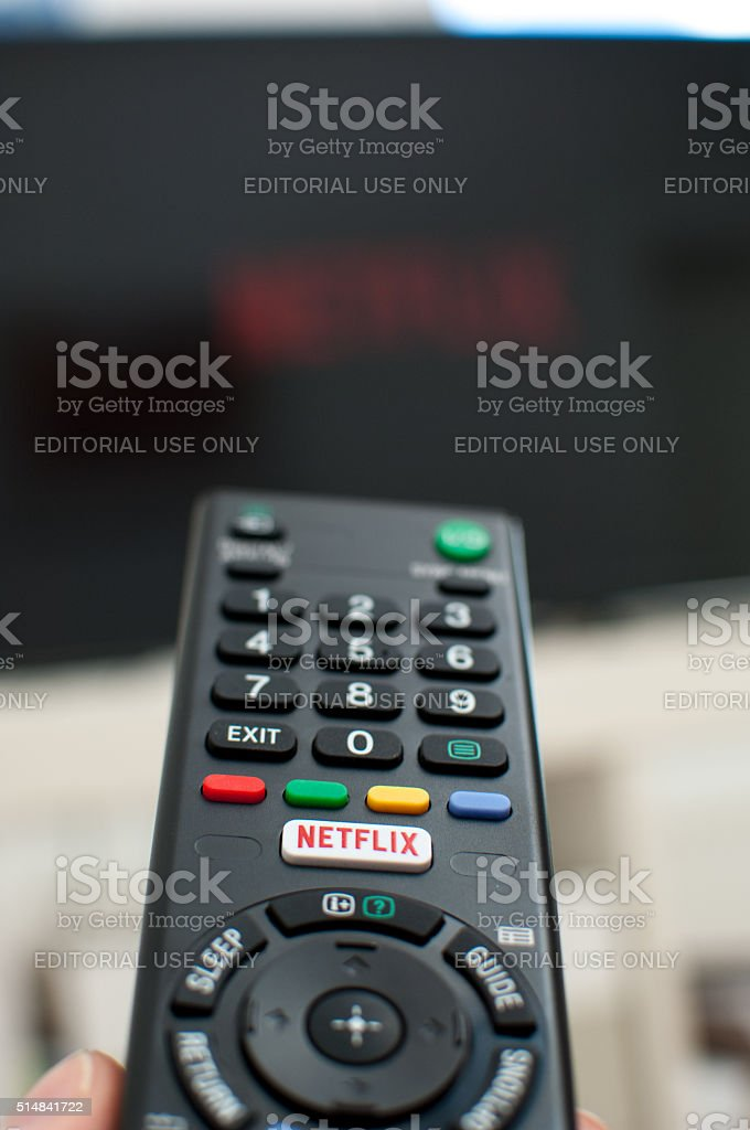 Netflix button on a TV remote with television. stock photo
