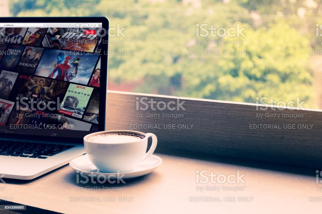 Netflix website showing on screen laptop with macbook pro at cafe. Netflix being popular internationally stock photo