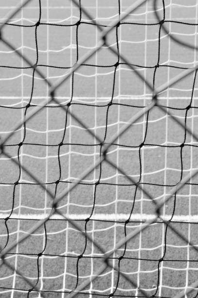Netting and fencing behind the goal of a football field View from behind the soccer goal werken stock pictures, royalty-free photos & images
