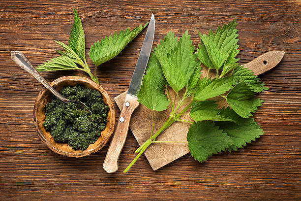 Nettle Nettle fresh green leaves on a wooden background. stinging nettle stock pictures, royalty-free photos & images
