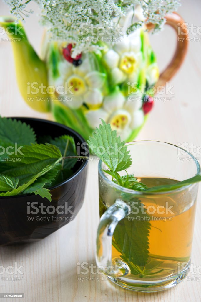 Nettle tea on a wooden table and wild flowers in a ceramic kettle stock photo