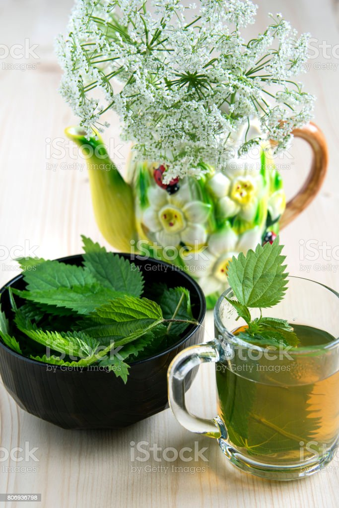 Nettle tea on a wooden table and wild flowers stock photo