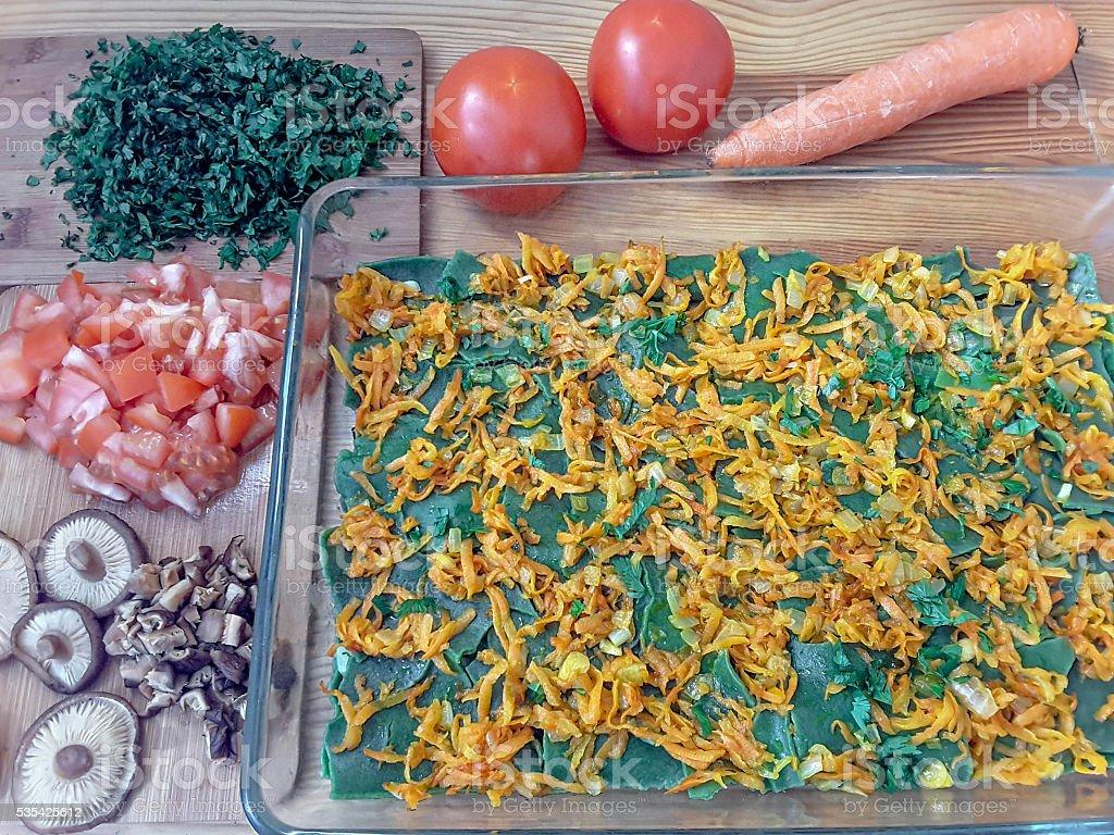 Зеленый лазанья кухни и крапивными растениями, грибами, помидоры и морковь стоковое фото