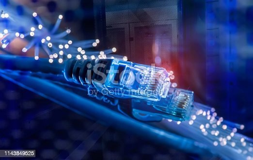istock Network cable with high tech technology Fiber optical color background 1143849525