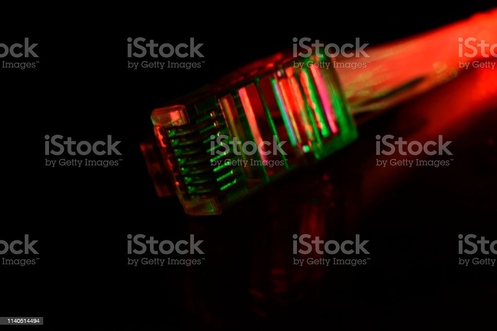 Network connection plug with optical fiber on black background