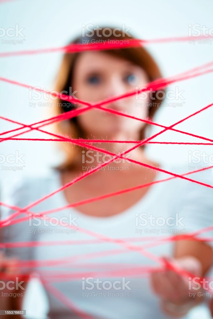 Network Network concept. Focus on the red rope with a woman in the background. Adult Stock Photo