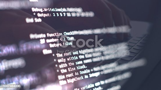 Computer language script and coding on screen with a man reflection in the background