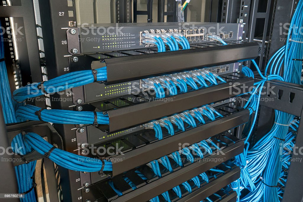 Network switch and ethernet cables in rack cabinet stock photo