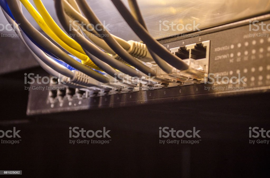 Network switch and ethernet cables, symbol of global communications. Colored network cables on dark background with lights and smoke. Selective focus royalty-free stock photo