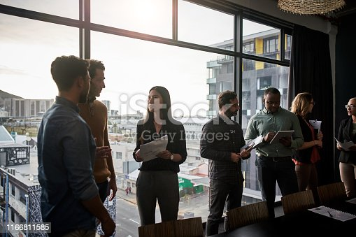 Shot of a group of businesspeople working and conversing together inside a modern office