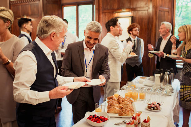Networking with Breakfast Business people plating up complimentary food while at a business conference. The group is talking and eating while networking. conference event stock pictures, royalty-free photos & images