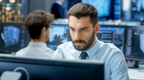 Neural Network and Machine Learning Engineer Programming at His Workstation. Office is Crowded With People Working. Multiple Displays Show Neural Network, Artificial Intelligence Representation. stock photo