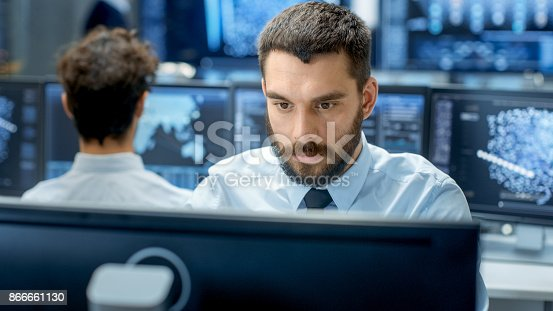 istock Neural Network and Machine Learning Engineer Programming at His Workstation. Office is Crowded With People Working. Multiple Displays Show Neural Network, Artificial Intelligence Representation. 866661130