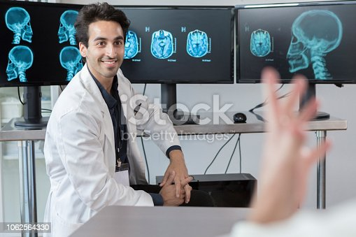 Confident male neurologist discusses a patient's brain x-rays with an unrecognizable colleague. The colleague is gesturing in the foreground.