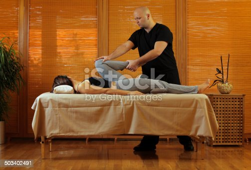 neuromuscular therapist massaging young man