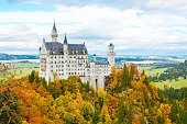 Neuschwanstein, Germany - October 19, 2016: Neuschwanstein Castle, Germany. Image of the famous tourist attraction surrounded with autumn colors during fall.