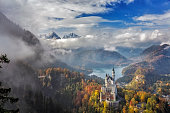 Fussen, Germany - October 17, 2015: Beautiful view of world-famous Neuschwanstein Castle, the nineteenth-century Romanesque Revival palace built for King Ludwig II on a rugged cliff, with scenic mountain landscape near Fussen, southwest Bavaria, Germany.