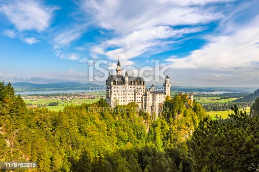 The beautiful castle of Neuschwanstein in Germany. This romanesque style historic construction was build by king Ludwig II of Bavaria on a hill surrounded by a beautiful landscape of mountains forest and lakes.