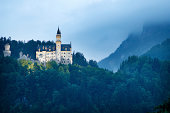 Hohenschwangau, Germany - July 4, 2013: Neuschwanstein castle on a hazy summer evening. The castle in southwest Bavaria near the city FAssen has been built by the former Bavarian King Ludwig II. 60 Million people have visited the castle since Ludwig's death in 1886.