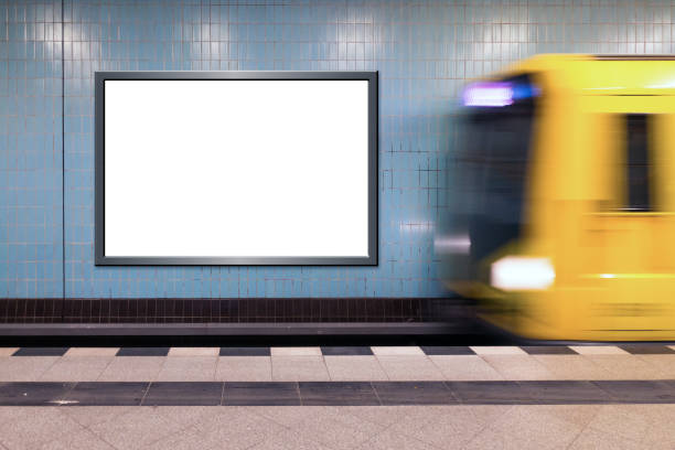 Neutral billboard in a subway station with incoming train Neutral billboard in the subway station with incoming yellow train underground stock pictures, royalty-free photos & images